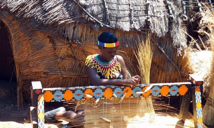 Eine Xhosa Frau beim Flechten