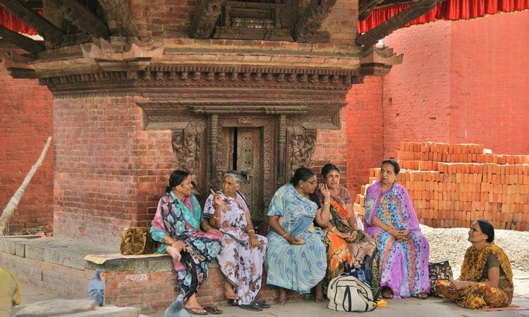 Alte Nepali Frauen plaudern vor dem kleinen Tempel