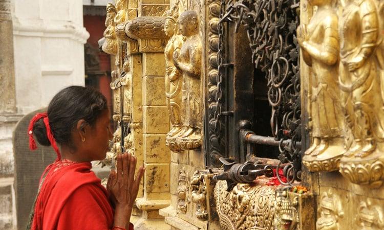 Eine Frau betet an einem der zahllosen Tempel der Stadt