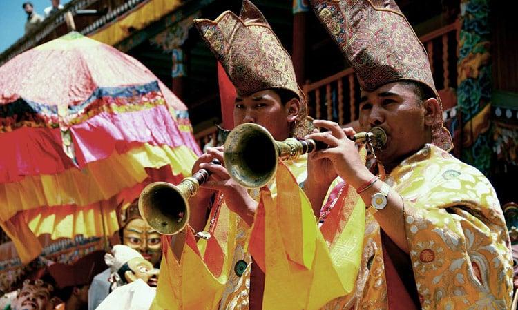 Moenche spielen auf dem Dungchen (Tibetanische Trompete).