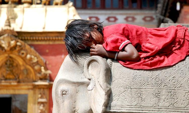 Ein Mädchen schläft auf dem Tempelelephant